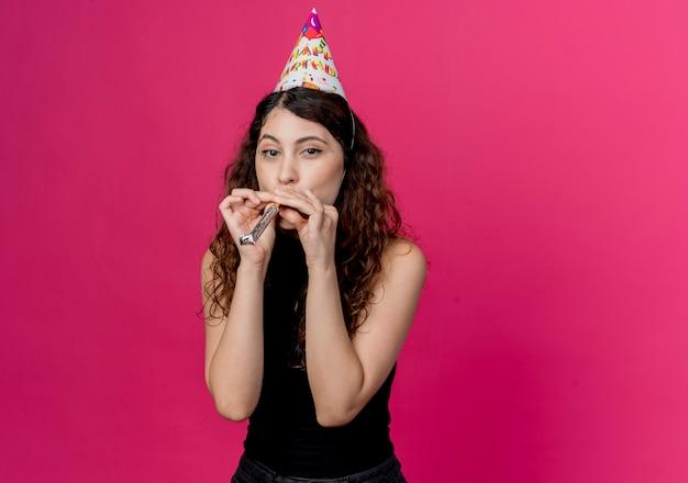 ピンクの壁の上に立って笛を吹く幸せでポジティブな誕生日パーティーのコンセプトホリデーキャップで巻き毛の若い美しい女性