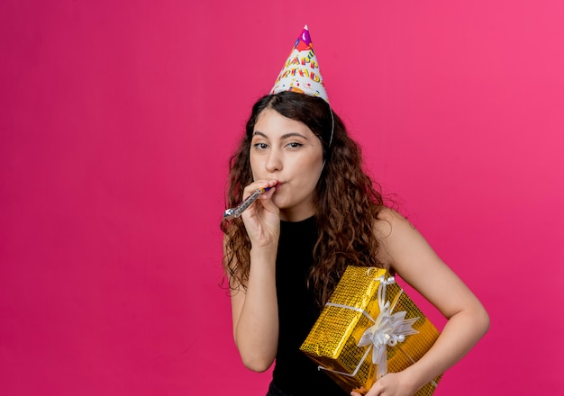 ピンクの壁の上に立っているギフトボックスの誕生日パーティーのコンセプトを保持している笛を吹くホリデーキャップで巻き毛の若い美しい女性