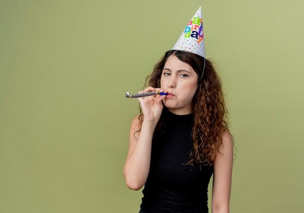 明るい壁の上に立っているカネラ不機嫌な誕生日パーティーのコンセプトを見て笛を吹くホリデーキャップで巻き毛の若い美しい女性
