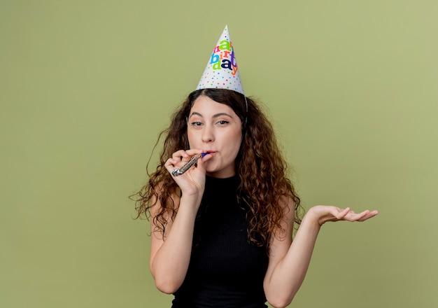 明るい壁の上に立っている誕生日パーティーのコンセプトを腕で口笛を吹くホリデーキャップで巻き毛の若い美しい女性