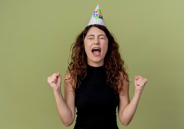 휴일 모자에 곱슬 머리를 가진 젊은 아름 다운 여자 주먹을 떨림 행복 하 고 가벼운 벽 위에 서 종료