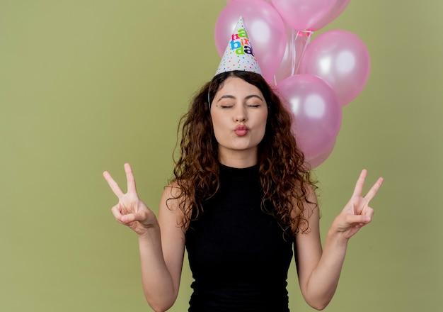 Молодая красивая женщина с вьющимися волосами в праздничной шапочке счастлива и позитивно показывает v-знак с закрытыми глазами, стоя с воздушными шарами над светлой стеной