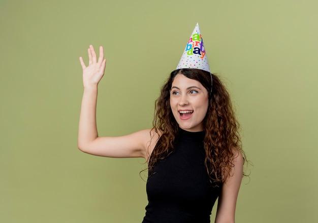 明るい壁の上に立っている手の誕生日パーティーのコンセプトで幸せで前向きな手を振ってホリデーキャップで巻き毛の若い美しい女性