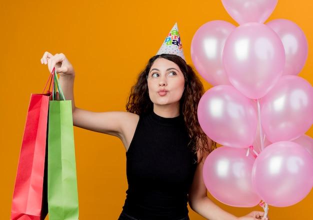 オレンジ色の壁の上に立っている空気と紙袋の誕生日パーティーのコンセプトを保持しているホリデーキャップで巻き毛の若い美しい女性