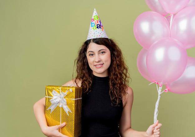Молодая красивая женщина с вьющимися волосами в праздничной шапочке держит воздушные шары и подарок на день рождения, улыбаясь счастливым лицом, стоя над светлой стеной