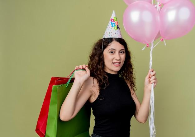 공기 풍선과 생일을 들고 휴가 모자에 곱슬 머리를 가진 젊은 아름 다운 여자는 행복하고 긍정적 인 밝은 벽 위에 유쾌하게 서 웃는 선물