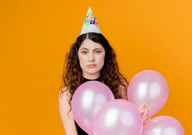 オレンジ色の壁の上に立って不機嫌と不幸な気球の誕生日パーティーのコンセプトを保持しているホリデーキャップで巻き毛の若い美しい女性