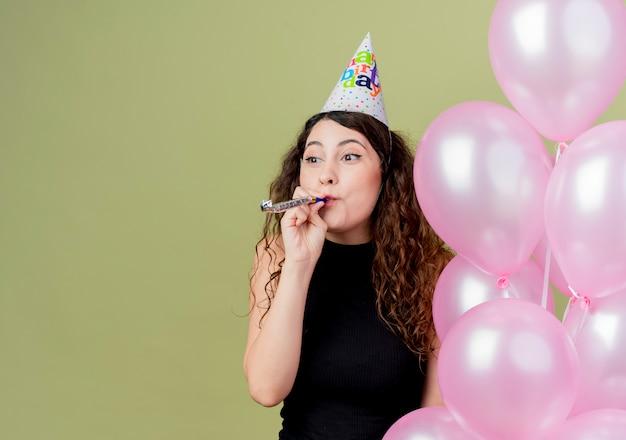밝은 벽에 서 행복하고 긍정적 인 축하 생일 파티를 불고 공기 풍선을 들고 휴일 모자에 곱슬 머리를 가진 젊은 아름 다운 여자