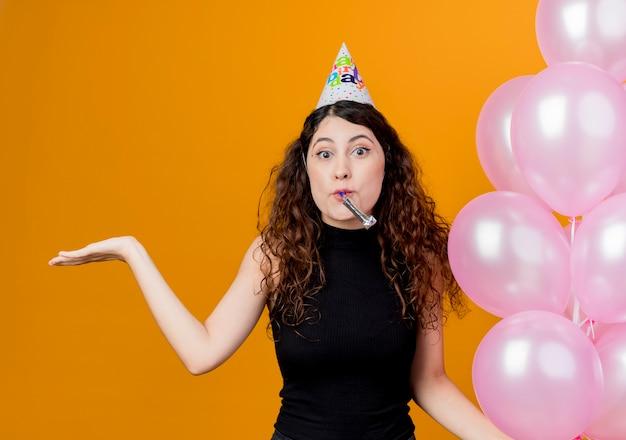 オレンジ色の壁の上に立っている側の誕生日パーティーのコンセプトに腕を広げて告白された笛を吹く気球を保持しているホリデーキャップで巻き毛の若い美しい女性