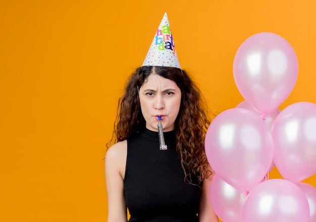 オレンジ色の壁の上に立っている不幸な顔の誕生日パーティーのコンセプトで笛を吹く気球を保持しているホリデーキャップで巻き毛の若い美しい女性