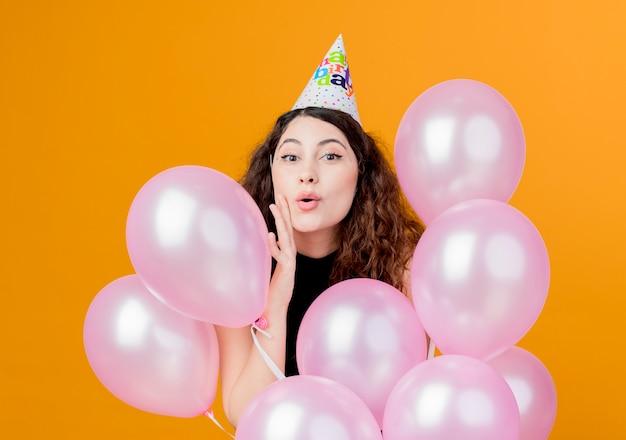 오렌지 벽 위에 서 공기 풍선 행복하고 흥분 생일 파티 개념을 들고 휴가 모자에 곱슬 머리를 가진 젊은 아름 다운 여자