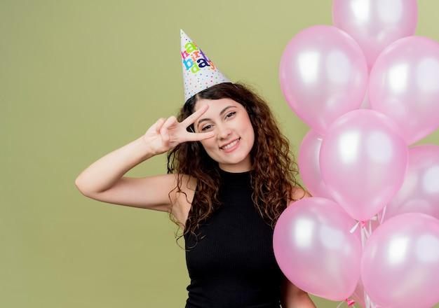 明るい壁の上に立っている誕生日パーティーを祝うvサインを示す幸せでポジティブな気球を保持しているホリデーキャップで巻き毛の若い美しい女性