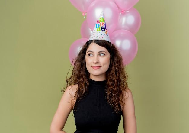 明るい壁の上に立っている顔の誕生日パーティーのコンセプトに笑顔で脇を見ている気球を保持しているホリデーキャップで巻き毛の若い美しい女性
