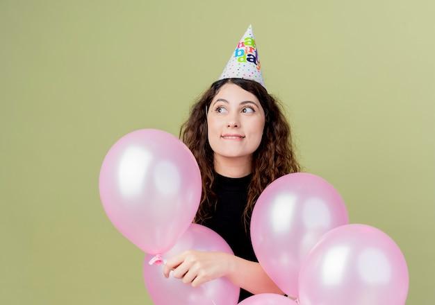 Молодая красивая женщина с вьющимися волосами в праздничной шапочке держит воздушные шары, глядя в сторону с улыбкой на лице, стоя над светлой стеной