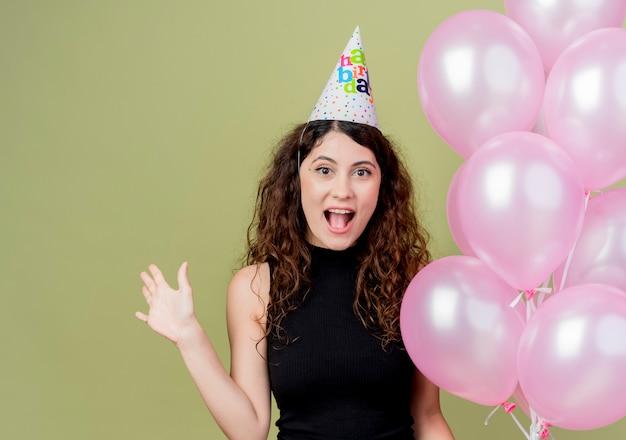 明るい壁の上に立っている陽気な誕生日パーティーのコンセプトを笑顔で幸せで興奮して手を上げる気球を保持しているホリデーキャップで巻き毛の若い美しい女性