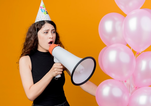 오렌지 벽 위에 서 확성기 생일 파티 개념을 외치는 공기 풍선을 들고 휴가 모자에 곱슬 머리를 가진 젊은 아름 다운 여자