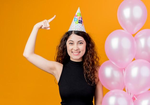 オレンジ色の壁の上に立っている人差し指幸せでポジティブな笑顔の誕生日パーティーのコンセプトを示す気球を保持しているホリデーキャップで巻き毛の若い美しい女性
