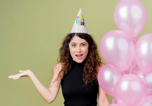 気球を保持しているホリデーキャップの巻き毛の若い美しい女性は、光の壁の上に立っている誕生日パーティーを驚かせて幸せに祝う