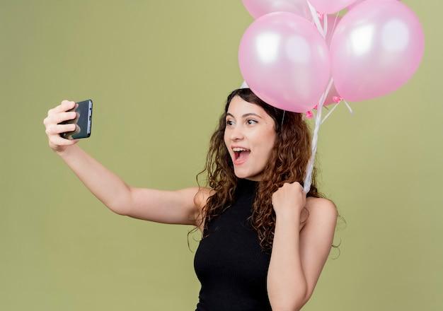 明るい壁の上に立っている幸せそうな顔の誕生日パーティーのコンセプトで笑顔でselfieを取っている気球を保持しているホリデーキャップで巻き毛の若い美しい女性