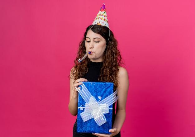 핑크 벽 위에 서있는 휘파람 생일 파티 개념을 불고 생일 상자를 들고 휴가 모자에 곱슬 머리를 가진 젊은 아름 다운 여자