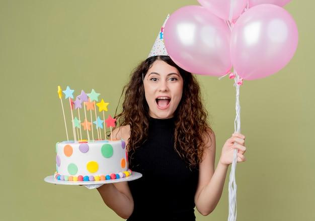 Молодая красивая женщина с вьющимися волосами в праздничной шапочке держит праздничный торт и воздушные шары, весело и радостно улыбаясь, стоя над светлой стеной