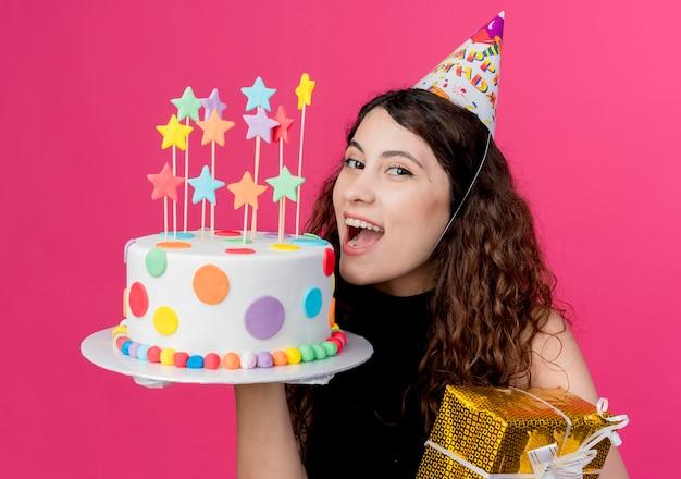 Молодая красивая женщина с вьющимися волосами в праздничной шапочке держит торт на день рождения и подарочную коробку счастливая и взволнованная концепция вечеринки по случаю дня рождения над розовым