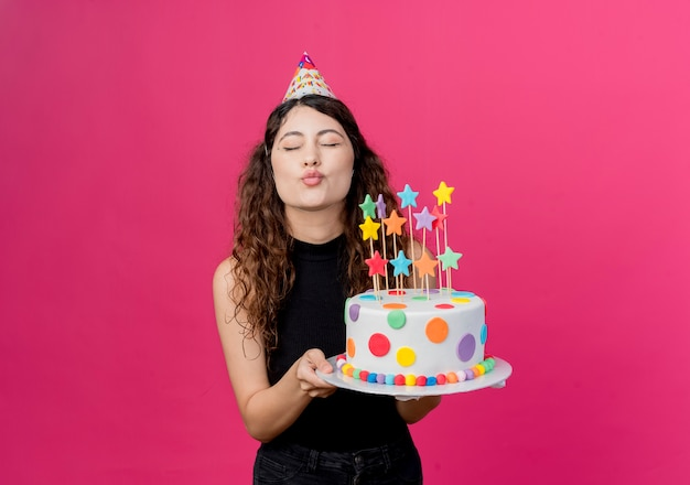 ピンクの壁の上に立ってキスの誕生日パーティーのコンセプトを吹くバースデーケーキを保持しているホリデーキャップの巻き毛の若い美しい女性