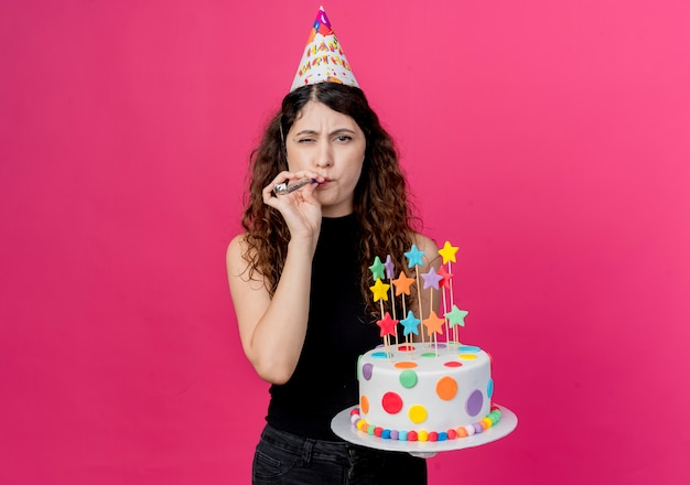 Молодая красивая женщина с вьющимися волосами в праздничной шапочке держит свисток для торта на день рождения, счастливая и позитивная концепция вечеринки по случаю дня рождения, стоящая над розовой стеной