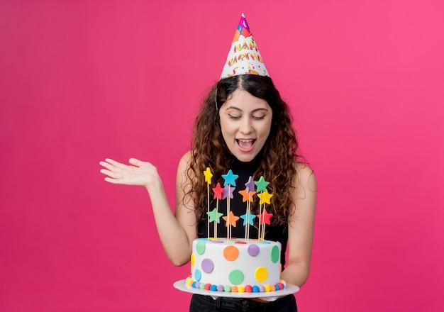 ピンクの壁の上に立っている誕生日ケーキ幸せで興奮した誕生日パーティーのコンセプトを保持しているホリデーキャップの巻き毛の若い美しい女性