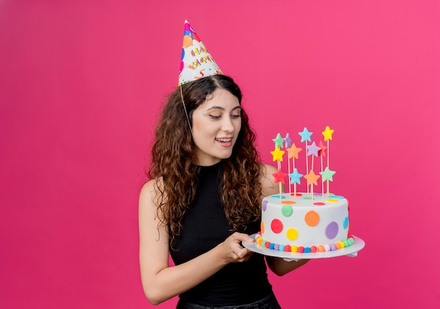 핑크를 통해 생일 케이크 행복하고 긍정적 인 생일 파티 개념을 들고 휴가 모자에 곱슬 머리를 가진 젊은 아름 다운 여자