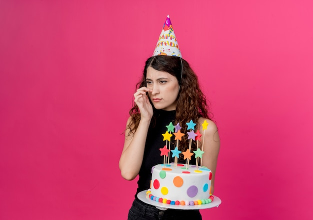 ピンクの壁の上に立っている混乱した誕生日パーティーのコンセプトを脇に見てバースデーケーキを保持しているホリデーキャップの巻き毛の若い美しい女性