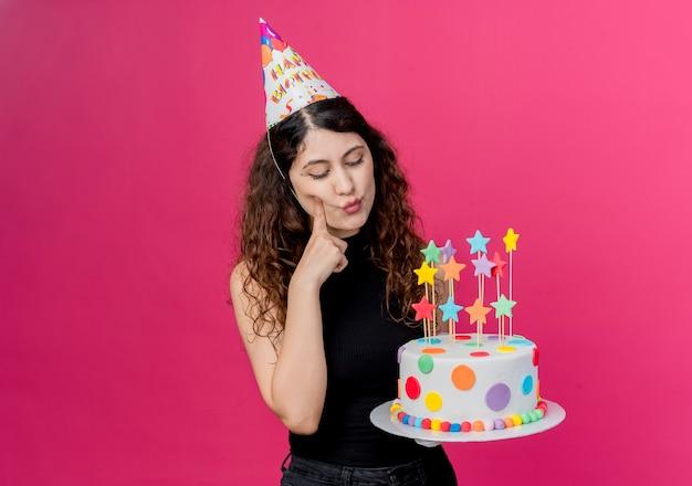 ピンクの壁の上に立っている困惑した誕生日パーティーのコンセプトを見て誕生日ケーキを保持しているホリデーキャップで巻き毛の若い美しい女性