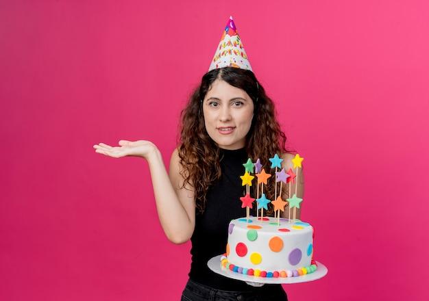 ピンクの壁の上に立っている混乱した肩をすくめる肩の誕生日パーティーのコンセプトを探しているバースデーケーキを保持している休日の帽子の巻き毛の若い美しい女性