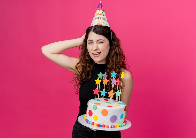 ピンクの壁の上に立っている彼女の頭の誕生日パーティーのコンセプトに手と混乱しているように見えるバースデーケーキを保持しているホリデーキャップの巻き毛の若い美しい女性