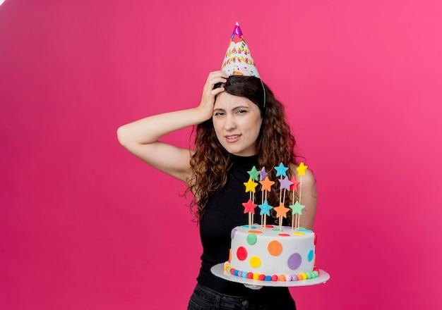 분홍색 벽 위에 서 그녀의 머리 생일 파티 개념에 손으로 혼란 찾고 생일 케이크를 들고 휴가 모자에 곱슬 머리를 가진 젊은 아름 다운 여자