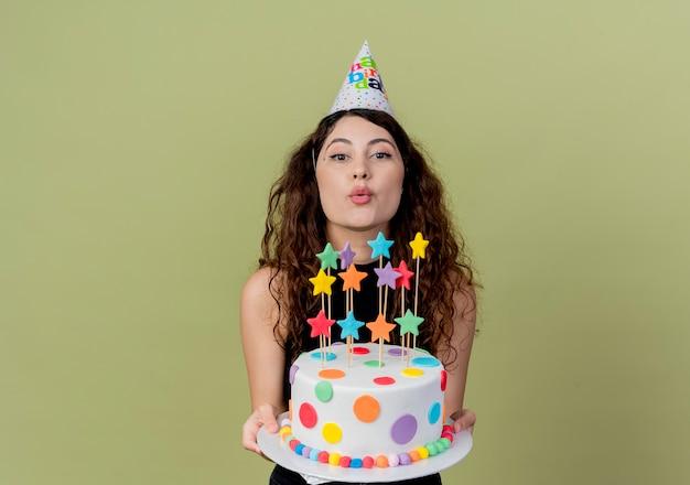 Молодая красивая женщина с вьющимися волосами в праздничной шапочке держит торт ко дню рождения, весело и радостно улыбаясь над светом