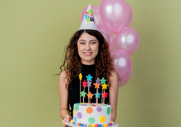 明るい壁の上に立って元気に幸せで楽しい笑顔のバースデーケーキを保持しているホリデーキャップで巻き毛の若い美しい女性