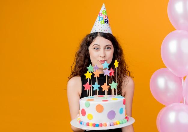 オレンジ色の壁の上の風船で元気に幸せで楽しい立って笑顔のバースデーケーキを保持しているホリデーキャップで巻き毛の若い美しい女性