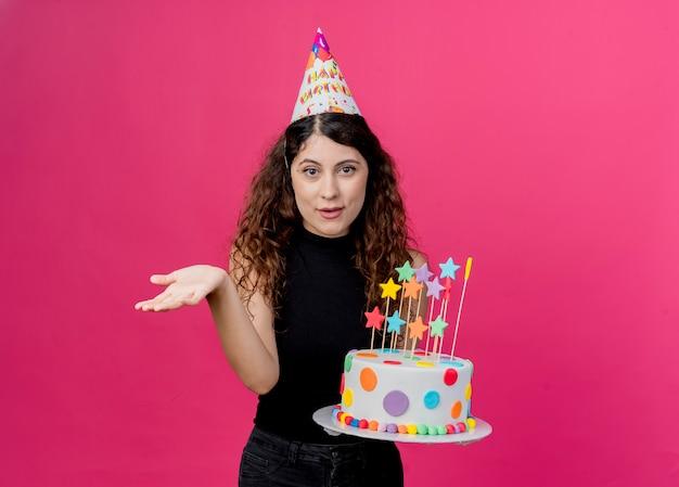 ピンクの壁の上に立っている誕生日パーティーのコンセプトを尋ねるように腕を出して笑っているバースデーケーキを保持しているホリデーキャップの巻き毛の若い美しい女性