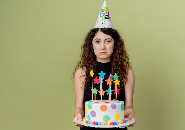Молодая красивая женщина с вьющимися волосами в праздничной шапочке держит праздничный торт с грустным выражением лица, стоя над светлой стеной