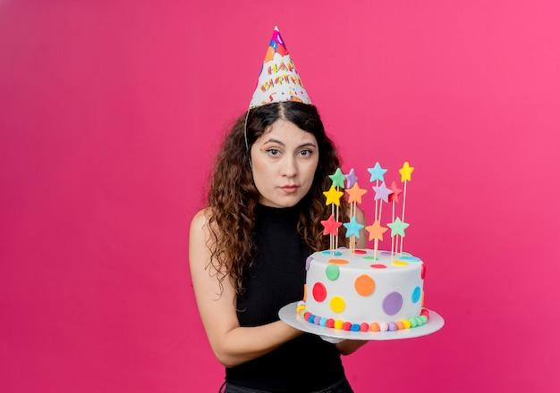 ピンクの壁の上に立っている深刻な顔の誕生日パーティーのコンセプトでバースデーケーキを保持している休日の帽子の巻き毛の若い美しい女性