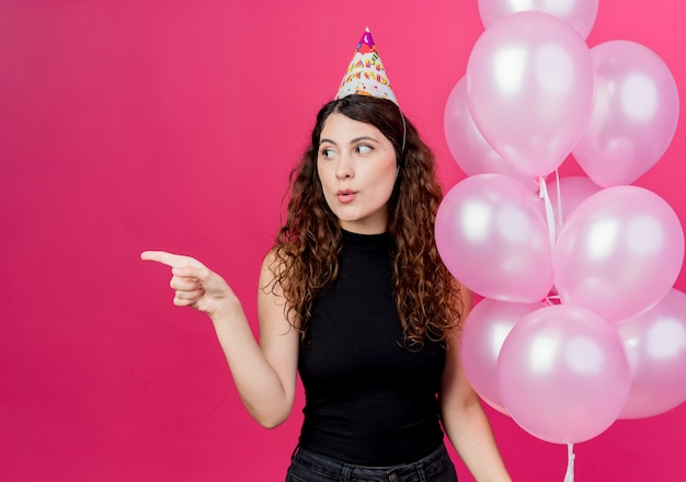 ピンクの壁の上に立っている側の誕生日パーティーのコンセプトを指で指している気球の束を保持しているホリデーキャップの巻き毛の若い美しい女性
