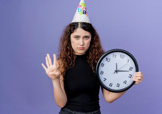 Молодая красивая женщина с вьющимися волосами в праздничной кепке держит настенные часы, показывающие номер четыре с грустным выражением лица, концепция вечеринки по случаю дня рождения, стоящая над синей стеной