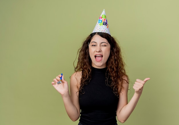 明るい壁の上に立っている誕生日パーティーのコンセプトを親指で示して幸せで興奮した笛を保持しているホリデーキャップで巻き毛の若い美しい女性