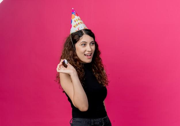 핑크 벽 위에 서 휘파람 행복하고 긍정적 인 생일 파티 개념을 들고 휴가 모자에 곱슬 머리를 가진 젊은 아름 다운 여자
