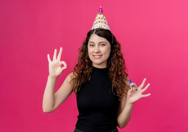ピンクの壁の上に立っている陽気な誕生日パーティーのコンセプトを笑顔でokサインを示す笛を保持しているホリデーキャップで巻き毛の若い美しい女性