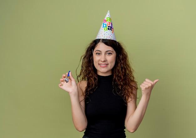 明るい壁の上に立って元気に笑顔の誕生日パーティーのコンセプトの笛を保持しているホリデーキャップで巻き毛の若い美しい女性