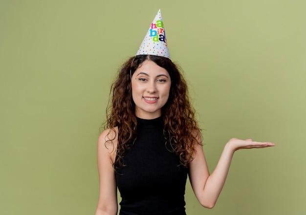 오렌지 벽 위에 서 웃는 생일 파티 개념의 팔을 제시하는 휴가 모자에 곱슬 머리를 가진 젊은 아름 다운 여자