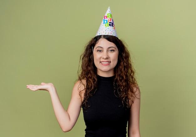 明るい壁の上に立って元気に誕生日パーティーのコンセプトを笑顔の手の腕を提示ホリデーキャップで巻き毛の若い美しい女性