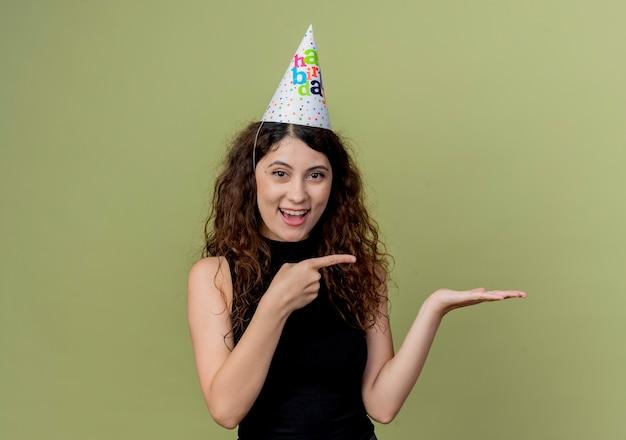휴일 모자에 곱슬 머리를 가진 젊은 아름 다운 여자는 빛을 통해 손 생일 파티 개념의 팔을 제시하는 측면을 손가락으로 가리키는 미소